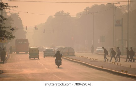 Vehicles and people moving in the streets amidst heavy smog.