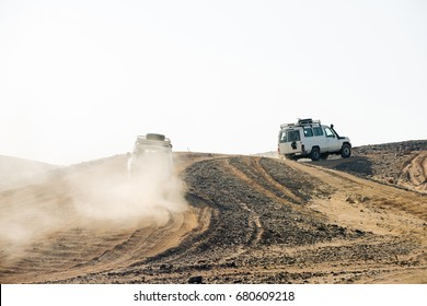Vehicles racing through desert hills on dusty sand road on white sky background. Dune bashing. Safari trip. Offroad adventure. Travel, travelling. Summer vacation