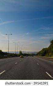 vehicles using a quite freeway driving towards city haze