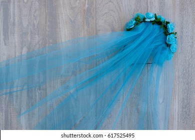 The veil is blue. Tulle gathered in a veil. A veil is attached to the hair hoop. Wrap for hair in the form of a wreath. Blue tulle on a gray background. A veil made of mesh fabric. View from above.