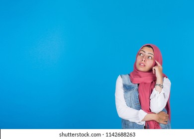 Veiled girl standing finger on forehead looking up thinking on a blue background.