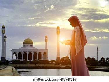 8582882ad41b Veiled Islamic muslim woman wearing a burka standing and praying in a beam  of overhead light