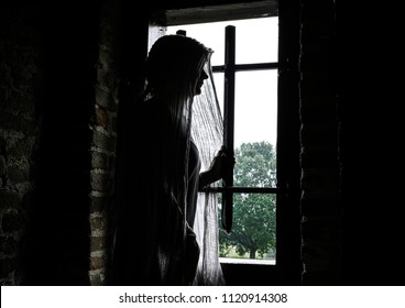 Veiled medieval woman staring out of the window of her castle.