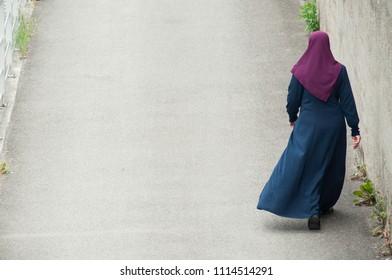 Veiled Muslim woman walking in the street on back view
