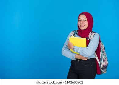 Veiled student hugs yellow book carrying backpack smiling, on a blue background.