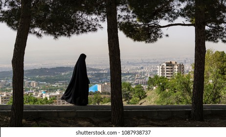 veiled woman with the background of Tehran city aerial view, Iran