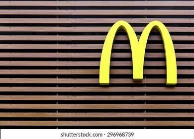 Vejle, Denmark - July 4, 2015: Mc Donald's logo on a striped facade. McDonald's is the world's largest chain of hamburger fast food restaurants