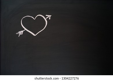 Velentines Day heart with an arrow on a blackboard with copyspace