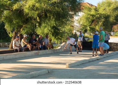 VELI IZ, CROATIA - AUGUST 23, 2014: Group of senior citizens playing game of boules  on the playing field. Boules is popular recreational activity of senior citizens in Dalmatia region of Croatia.
