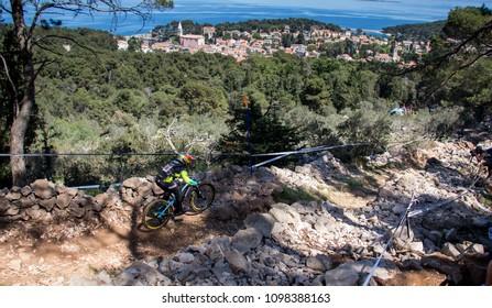 Veli Losinj, Croatia - April 21 2018: Downhill World Cup racer on the track, with beautiful Veli Losinj in the background.