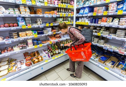 Veliky Novgorod, Russia - August 17, 2017: Young woman choosing salmon fish at shopping in chain supermarket