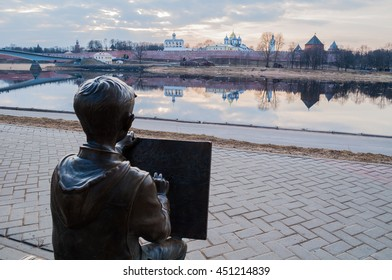 VELIKY NOVGOROD, RUSSIA -MARCH 26, 2016. Architecture landscape spring view - sculpture of the painter boy drawing the Novgorod Kremlin in front of the Volkhov river in Veliky Novgorod, Russia
