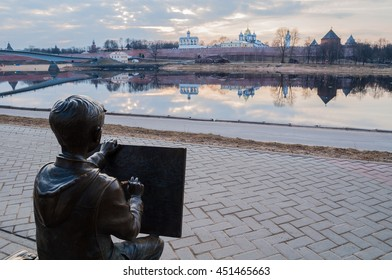 VELIKY NOVGOROD, RUSSIA -MARCH 26, 2016. Architecture landscape - sculpture of the painter boy drawing the Novgorod Kremlin in front of the Volkhov river. Selective focus at the sculpture