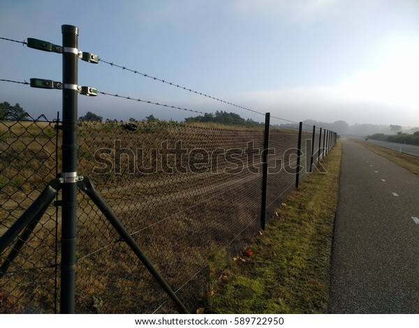 VELUWE, THE NETHERLANDS - DECEMBER 2016: Fence alongside cycle path and road through Veluwe national park, to prevent wildlife vehicle collisions