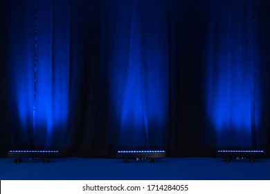 Velvet blue theatre curtains lit by three led uplights