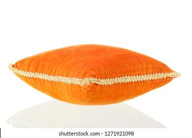 Velvet orange pillow with golden ribbon isolated over white background