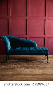Velvet turquoise sofa on the background of a burgundy wall
