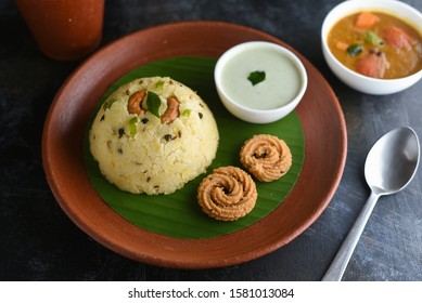 Ven Pongal with Sambar, coconut Chutney popular Indian breakfast food Tamil Nadu festival Pongal made with Rava or semolina in clay or terracotta plate dark black background top view, South India.