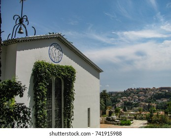 Vence, Provence Alpes Maritimes Cote d' Azur, France - August 3, 2011: One end of Chapelle du Rosaire with decorative tile figures by the building's designer, Henri Matisse. Beyond it a view of Vence.