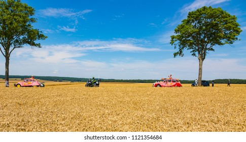 Vendeuvre-sur-Barse, France - 6 July, 2017: Two vehicles of Cochonou passes through a region of wheat fields in the Publicity Caravan before the cyclists during the stage 6 of Tour de France 2017.