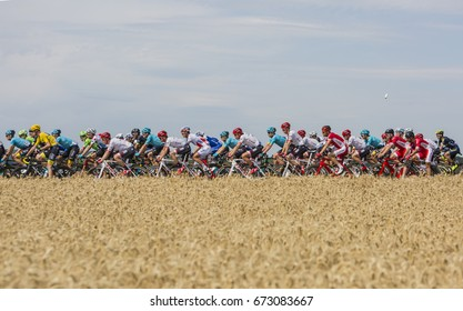 VENDEUVRE-SUR-BARSE, FRANCE - JUL 6: A cyclist's water-can flies over the peloton passing through a region of wheat fields during the stage 6 of Tour de France 2017.