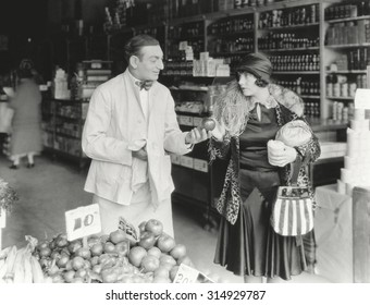 Vendor bargaining with woman at market