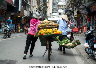 Vendor with bike of fruits on Hanoi street