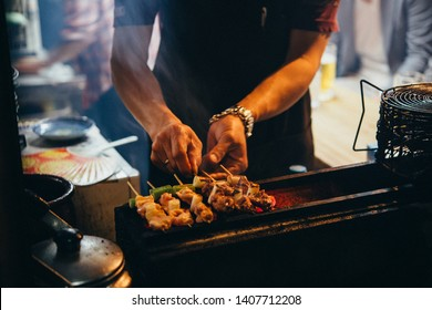 A vendor is grilling scallops for sale  in one of the small bars of of Omoide Yokocho in Tokyo, Japan.