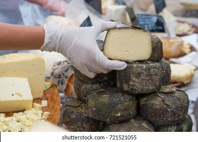 Vendor hands holding natural crafted organic cheese on the market