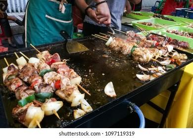 Vendor preparing grilled kebab chicken at market stall for iftar or buka puasa in Malaysia during Ramadan fasting month