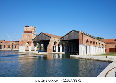 Venetian Arsenal with docks, canal and arcade, blue sky in summer in Venice, Italy