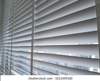 A venetian blind in white tone. There is landscape in the background.