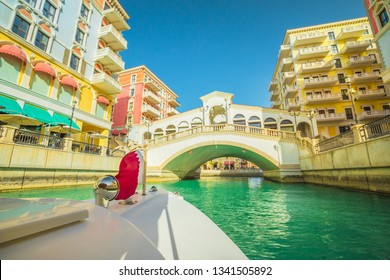 Venetian bridge on canals of picturesque Qanat Quartier icon of Doha, Qatar from a touristic boat with flag of Qatar. Venice at the Pearl, Persian Gulf, Middle East. Famous attraction at sunset light.