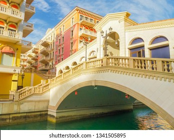 Venetian bridge on canals of picturesque district of Doha, Qatar. Venice at Qanat Quartier in the Pearl-Qatar, Persian Gulf, Middle East. Famous tourist attraction at sunset light.