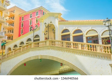 Venetian bridge of picturesque district of Doha, Qatar. Venice at Qanat Quartier in the Pearl-Qatar, Persian Gulf, Middle East. Famous tourist attraction at sunlight. Travel in Qatar.