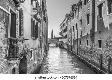Venetian canal Rio de la Pleto. Old walls with balcony and architecturical elements. Venice, Veneto, Italy. Black and white photography.