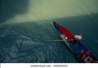 venetian gondola on river photographed from above with italian man on boat warm colors sunny