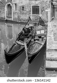 Venetian gondolas in anticipation of passengers at the embankment of the channel - Venice, Italy (black and white)