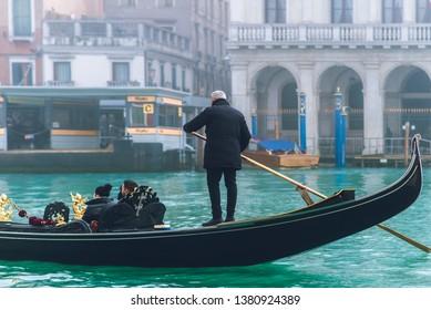 Venetian gondolier (boatman) rowing gondola in fog