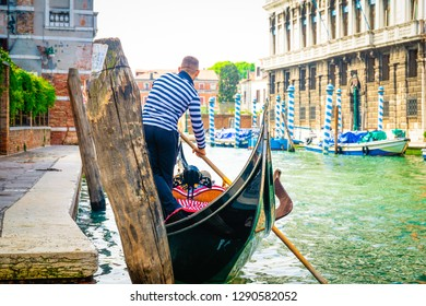 Venetian gondolier getting ready for punting in Venice
