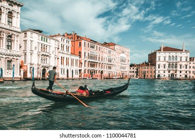 Venetian gondolier punting gondola through grand canal of Venice, Italy. Gondola is a traditional, flat-bottomed Venetian rowing boat. It is the unique transportation of Venice, Italy.