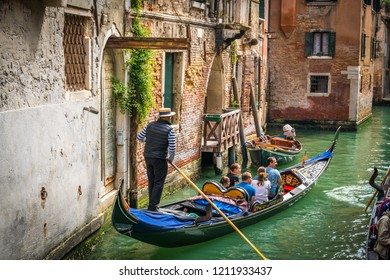 Venetian gondolier punting gondola through green canal with tourists on board:VENICE, ITALY-OCTOBER 10, 2018
