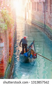 Venetian gondolier punting gondola through green canal waters - Tourists travel on gondolas at canal - Venice, Italy