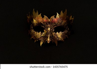 Venetian mask in gold and red with metallic pieces in the form of leaves. original and unique design, handmade crafts