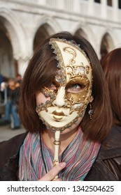 Venetian mask on the tourist woman. Woman with white mask. Beautiful green eyes behind the mask.