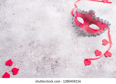 venetian mask and valentines hearts on stone background. Blind date concept, copy space
