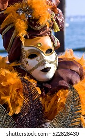 Venetian Mask. Venice, Italy - March 5, 2011: Street performer posing for tourists in a traditional mask near to St. Mark's Square during the carnival celebration.
