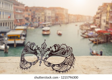 Venetian masks on bridge agaist landscape Grand Canal with gondolas and boats in Venice, Italy . Annual carnival in Venice is among the most famous in Europe. Venice is a popular tourist destination