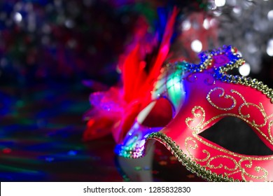 Venetian red mask on defocused carnival party background