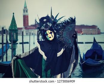 Venezia, Italia - February 13 2018: carnivale mask, morning light with gondolas and church